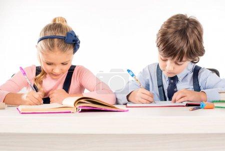 Classmates writing homework in notebooks
