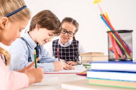 Photo pour Enfants étudiant ensemble et écrivant dans des cahiers - image libre de droit