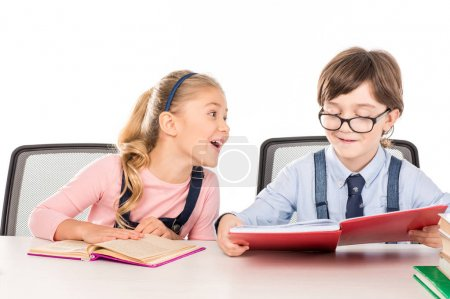 Photo for Happy schoolchildren sitting at the table and preparing homework together isolated on white - Royalty Free Image