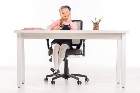 Smiling schoolgirl sitting at desk with books