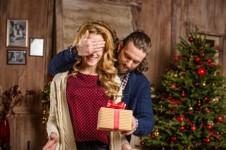 Photo for Handsome man giving christmas present to smiling blonde woman in cozy room - Royalty Free Image