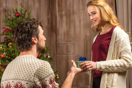Photo for Kneeling man presenting gift box to smiling woman - Royalty Free Image