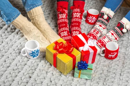 Legs in knitted socks and christmas presents