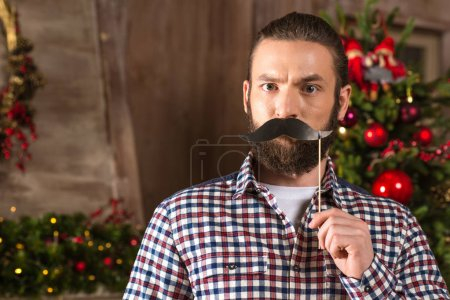 Serious man holding paper moustache