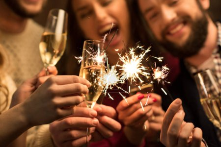 Photo for Close-up view of happy people with glasses of champagne and sparklers - Royalty Free Image
