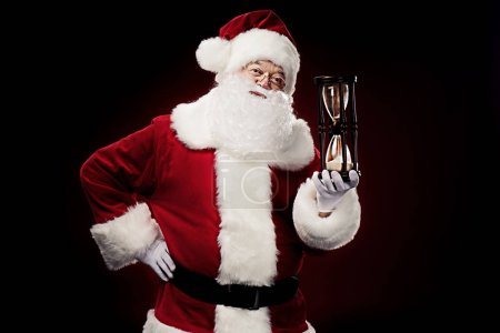 Santa Claus showing big hourglass