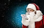 Santa Claus foukání sněhové vločky
