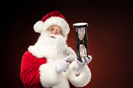 Santa Claus pointing on hourglass