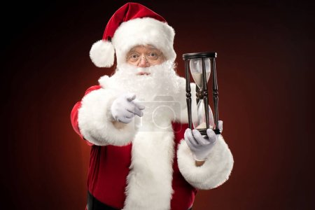 Santa Claus with hourglass pointing at camera