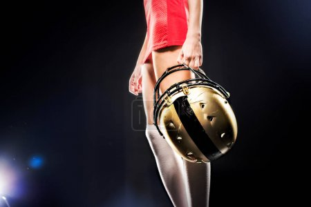 Female football player holding helmet