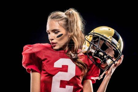 Female football player posing with helmet