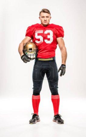 Football player holding helmet