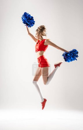 Cheerleader jumping with pom-poms