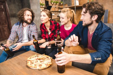 Friends drinking beer and eating pizza