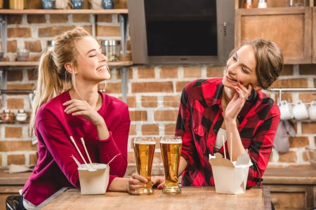 Happy women with noodles and beer