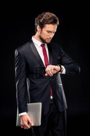 Handsome businessman holding laptop