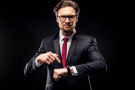 Businessman pointing at wristwatch