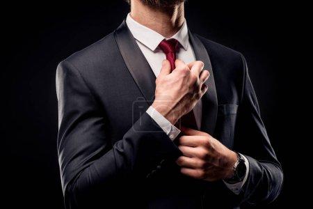 Businessman adjusting tie