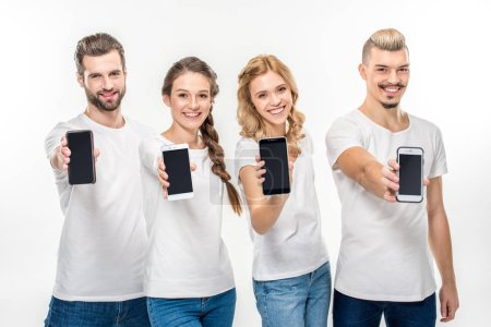 Smiling young people showing smartphones