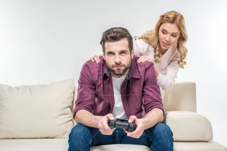 Woman looking at man playing with joystick