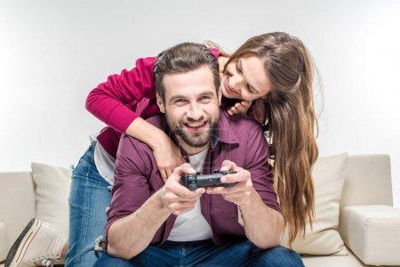 Woman hugging man playing with joystick