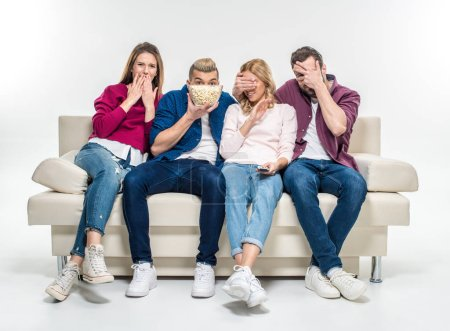 Friends sitting on couch with popcorn