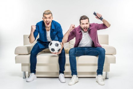 Friends sitting on couch with soccer ball