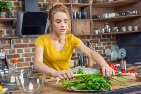 Woman holding green onions