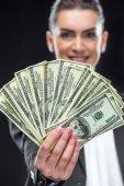 Podnikatelka drží dolarové bankovky