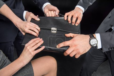 Businesspeople fighting for briefcase