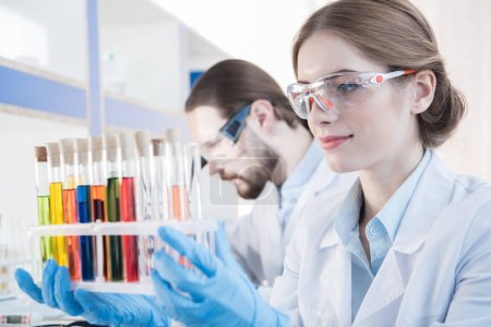 Scientist looking on test tubes
