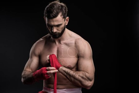 Sportsman wrapping hand in boxing bandage