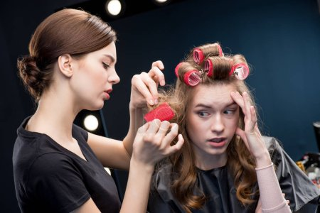 Hairstylist curling hair to woman