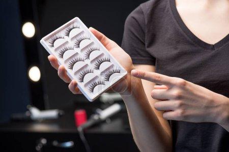 Makeup artist holding false eyelashes