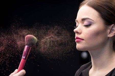 Make-up artist sprinkling face of model