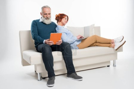Couple using laptop and digital tablet
