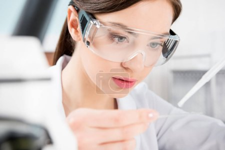 Female scientist in protective glasses