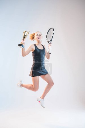 Woman with racket and trophy