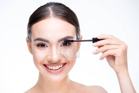 Woman painting eyelashes by mascara