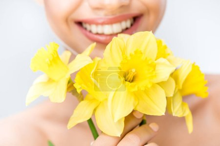 Woman holding yellow daffodils