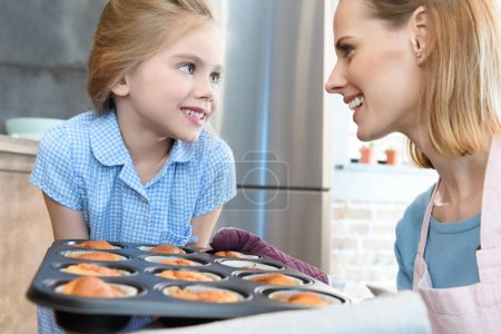 Mother and daughter baking cupcakes