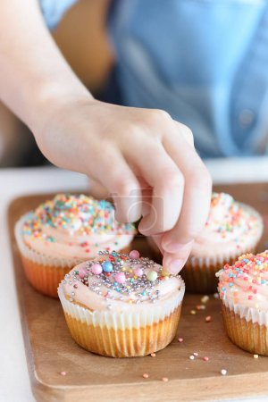 Girl putting confetti on cupcakes
