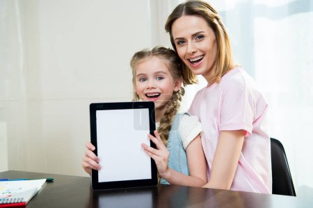 Mother and daughter showing digital tablet