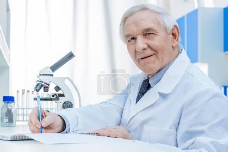 Senior chemists writing in notepad