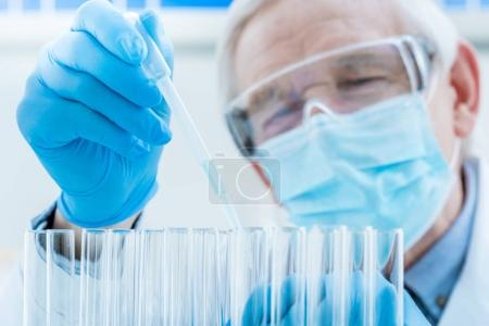 Senior chemist with test tubes