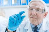 Senior scientist holding medicine
