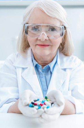 Senior scientist holding medicines