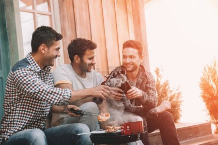 Friends drinking beer and making barbecue