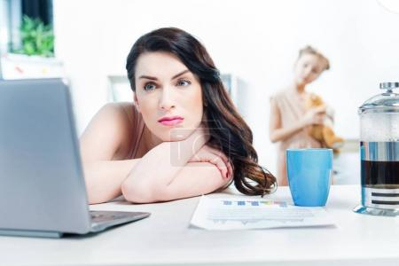 pensive businesswoman with laptop