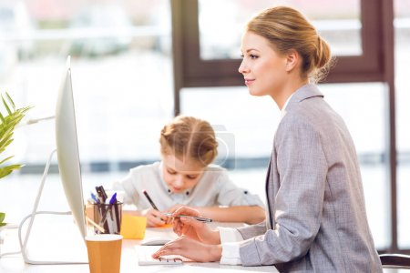 Mother working while daughter drawing